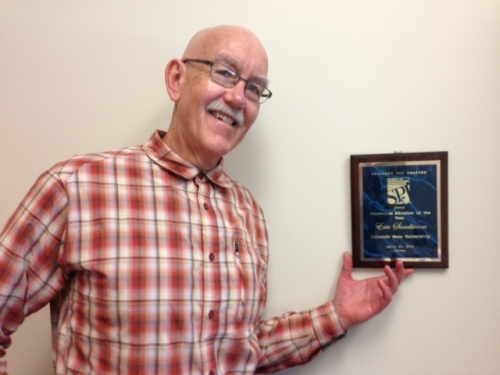 Colorado Mesa University journalism professor Eric Sandstrom is pictured in his office with the 2014 SPJ Colorado Pro Chapter Journalism Educator of the Year award he received in April. Sandstrom, adviser to the CMU student SPJ chapter and to the campus newspaper, hosted an SPJ visit on Oct. 6 at CMU.